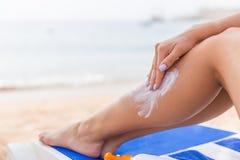 De jonge vrouw heeft rust op sunbed bij het strand en beschermt haar huid van toepassing zijnd sunblock op haar been royalty-vrije stock foto's
