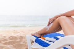 De jonge vrouw heeft rust op sunbed bij het strand en beschermt haar huid van toepassing zijnd sunblock op haar been stock fotografie