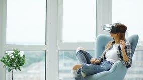De jonge vrouw heeft VR-ervaring die de virtuele zitting van de werkelijkheidshoofdtelefoon als voorzitter op balkon gebruiken royalty-vrije stock afbeeldingen