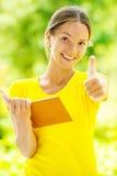 De jonge vrouw heft naar omhoog duim op Stock Afbeelding