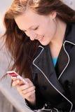 De jonge vrouw het draaien telefoon van de aantalcel Stock Foto's