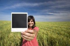 De jonge vrouw het glimlachen film van holdings enige polaroid Royalty-vrije Stock Afbeeldingen