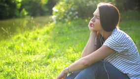 De jonge vrouw is het luisteren muziek die oortelefoons in openlucht met behulp van Het mooie meisje in gestreept overhemd geniet stock videobeelden