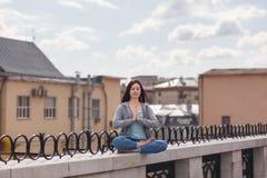 De jonge vrouw in het ontspannen stelt op de verschansing Stock Foto's