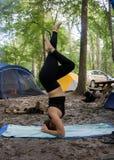 De jonge vrouw het praktizeren yoga in een headstand stelt terwijl het kamperen in het bos met zwarte uitrusting stock fotografie