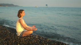 De jonge vrouw het praktizeren yoga op het strand en bespat plotseling een golf Zonsondergang stock videobeelden