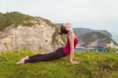 De jonge vrouw het praktizeren yogacobra stelt op de klip dichtbij de oceaan stock afbeelding