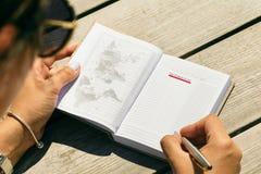 De jonge vrouw het schrijven plaatsen van de notitieboekjelijst zien conc Lijst van reis stock fotografie