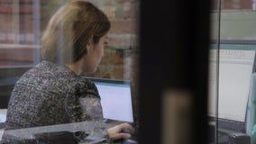 De jonge vrouw is het werken, zittend bij lijst met computer in groot bedrijf stock videobeelden
