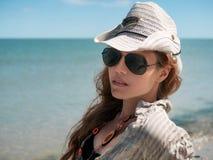 De jonge vrouw in hoed, zonnebril en overhemd zit bij de kust van de oceaan, overzees bij het zonnige dag Mooie Vrouw Lachen op d stock afbeelding