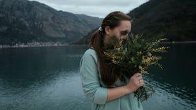 De jonge vrouw houdt boeket van mimosa, inhaleert geur dichtbij meer stock videobeelden