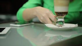 De jonge vrouw houdt de zitting van de koffiekop bij de lijst met apparaten op de oppervlakte in de koffie stock footage