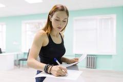 De jonge vrouw houdt een salon voor de zorg van handen en nagelt tekensdocumenten, zet een handtekening stock fotografie