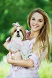 De jonge vrouw houdt hond haar wapens Royalty-vrije Stock Afbeelding