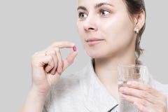 De jonge vrouw houdt rood vitaminetablet en glas water Co stock fotografie