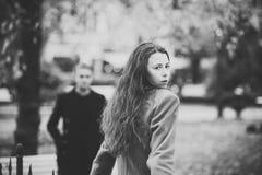 De jonge vrouw in kameellaag gaat naar vriend in park royalty-vrije stock afbeeldingen