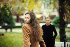 De jonge vrouw in kameellaag gaat naar vriend in park stock afbeeldingen