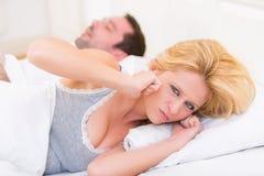 De jonge vrouw kan niet wegens het snurken van de vriend slapen Stock Foto