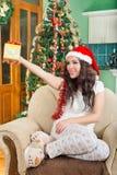 De jonge vrouw in Kerstmanhoed biedt giftdoos met lint aan Stock Afbeelding