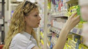 De jonge vrouw kiest babygoederen in de supermarkt stock footage