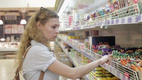 De jonge vrouw kiest babygoederen in de supermarkt stock video