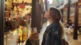 De jonge vrouw kiest de goederen in grote winkel stock videobeelden