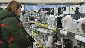 De jonge vrouw kiest een mixer in een supermarkt van huistoestellen stock videobeelden