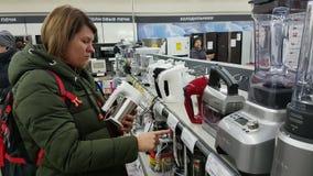 De jonge vrouw kiest een mixer in een supermarkt van huistoestellen stock footage