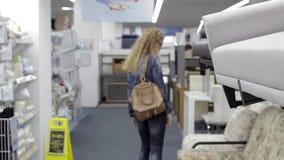 De jonge vrouw kiest goederen in de supermarkt stock footage