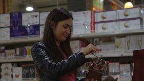 De jonge vrouw kiest herinneringen in de huishoudensectie bij de supermarkt stock video