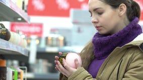 De jonge vrouw kiest kaarsen in een supermarkt stock videobeelden