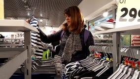 De jonge vrouw kiest kleren stock videobeelden