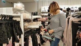 De jonge vrouw kiest kleren stock video