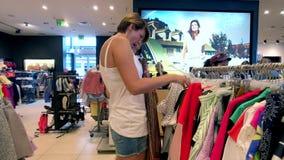 De jonge vrouw kiest kleren in de kledingswinkel stock video