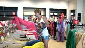 De jonge vrouw kiest kleren in de kledingswinkel stock footage