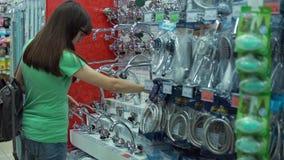 De jonge vrouw kiest mixerkraan in zelfbedieningswinkel stock videobeelden