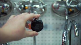 De jonge vrouw kiest mixerkraan in zelfbedieningswinkel stock footage