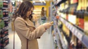 De jonge vrouw kiest roze wijn in een supermarktafdeling stock footage
