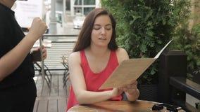 De jonge vrouw kiest schotel terwijl het zitten in de zomerkoffie stock videobeelden
