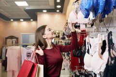 De jonge vrouw kiest sexy brassière onder reeks in een boutique Het mooie meisje denkt na de bustehouder met het winkelen zakken  royalty-vrije stock foto