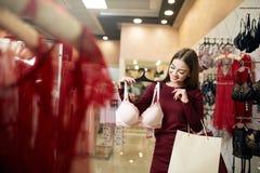 De jonge vrouw kiest sexy brassière onder reeks in een boutique Het mooie meisje denkt na de bustehouder met het winkelen zakken  stock fotografie