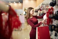 De jonge vrouw kiest sexy brassière onder reeks in een boutique Het mooie meisje denkt na de bustehouder met het winkelen zakken  royalty-vrije stock foto's