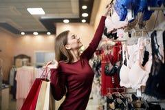 De jonge vrouw kiest sexy brassière onder reeks in een boutique Het mooie meisje denkt na de bustehouder met het winkelen zakken  stock foto's