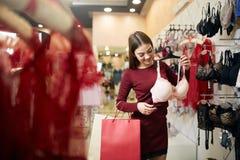 De jonge vrouw kiest sexy brassière onder reeks in een boutique Het mooie meisje denkt na de bustehouder met het winkelen zakken  stock afbeelding