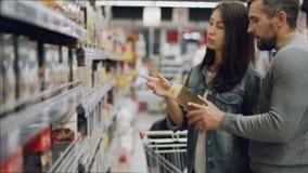 De jonge vrouw kiest thee in voedselopslag, helpen haar echtgenoot en zoon haar die producten en het spreken bekijken buying stock footage
