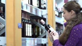 De jonge vrouw kiest wijn in een supermarkt stock video