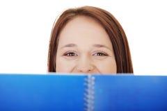 De jonge vrouw kijkt boven open notaboek. Royalty-vrije Stock Afbeelding