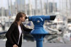 De jonge vrouw kijkt door telescoop Royalty-vrije Stock Foto's