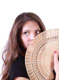 De jonge vrouw kijkt omhooggaand en verbergt haar mond door ventilator Stock Fotografie