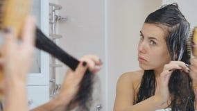 De jonge vrouw kijkt in de spiegel en kamt nat haar stock video